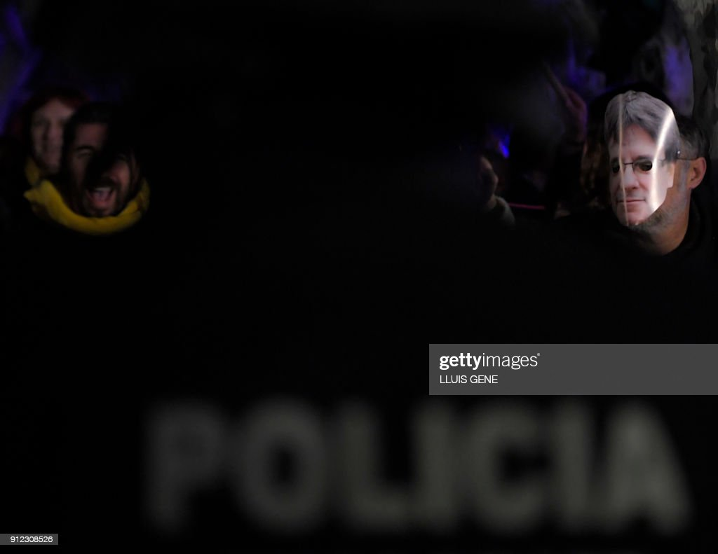 A person wearing a mask depicting ousted separatist leader Carles Puigdemont (R) stands with other demonstrators in front of police officers during a demonstration outside the Catalan parliament on January 30, 2018 in Barcelona. The speaker of Catalonia's parliament Roger Torrent delayed a key debate in the regional assembly on ousted separatist leader Carles Puigdemont's bid to form a new government, but defended his right to return to power. /