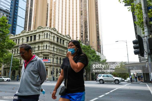 Person wearing a mask is seen walking past the Grand Hyatt on February 04, 2021 in Melbourne, Australia. Victoria has reintroduced COVID-19...