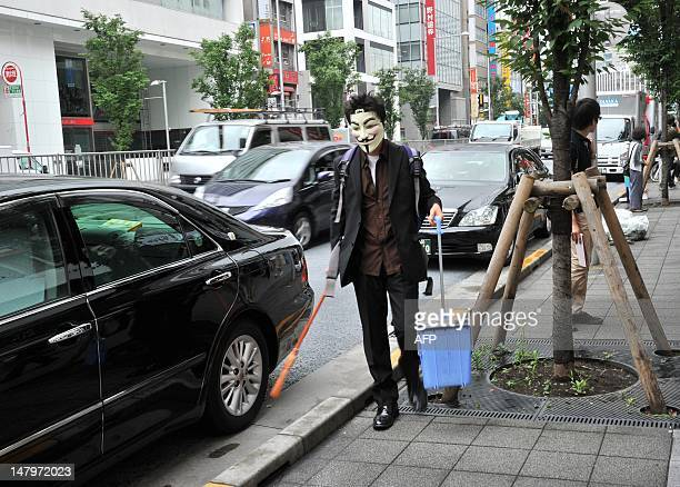 Person wearing a mask sweeps up litter as part of a clean up mission organised by hacker collective Anonymous on a street in Tokyo on July 7, 2012....