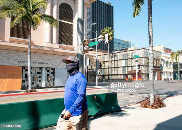 Person wearing a mask walks on Rodeo Drive in Beverly Hills, California on April 1, 2020 during the Covid 19 crisis. - All 40 million residents of...