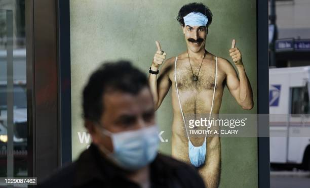 """Person wearing a mask walks past a bus stop ad on 5th Avenue, October 15 for the upcoming movie """"Borat 2,"""" featuring actor Sacha Baron Cohen, ahead..."""
