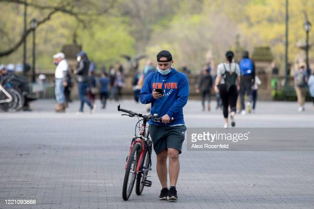 A person wearing a mask walks with his bike in Central Park as temperatures rose amid the coronavirus pandemic on April 25 2020 in New York City...