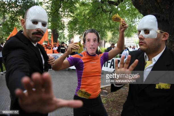A person wearing a mask with the face of Argentina's Minister of the Treasury Nicolas Dujovne demonstrates against the rise of public services fares...