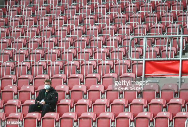 Person wearing a protective face mask is seen in the stands before the German first division Bundesliga football match FC Augsburg v 1. FC Cologne on...
