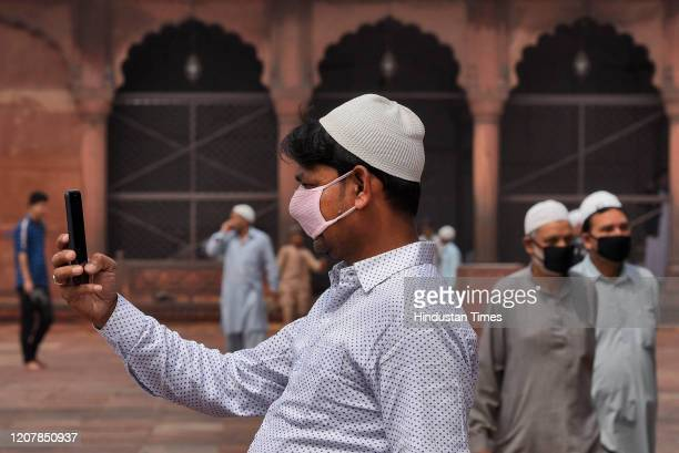 Person wearing a protective face mask takes a picture during Friday prayers amid Coronavirus outbreak in the country, at Jama Masjid on March 20,...