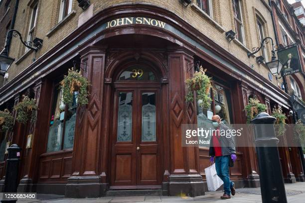 A person wearing a protective face mask walks past a temporarily closed pub named after the founding father of epidemiology John Snow on June 19 2020...