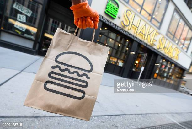 Person wearing a protective glove holds a bag outside Shake Shack during the coronavirus pandemic on April 20, 2020 in New York City. COVID-19 has...