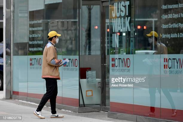 A person wearing a protective mask and gloves walk's into a CityMD amid the coronavirus pandemic on April 12 2020 in New York City United States...