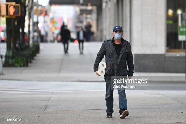 A person wearing a protective mask carries toilet paper amid the coronavirus pandemic on April 12 2020 in New York City United States COVID19 has...
