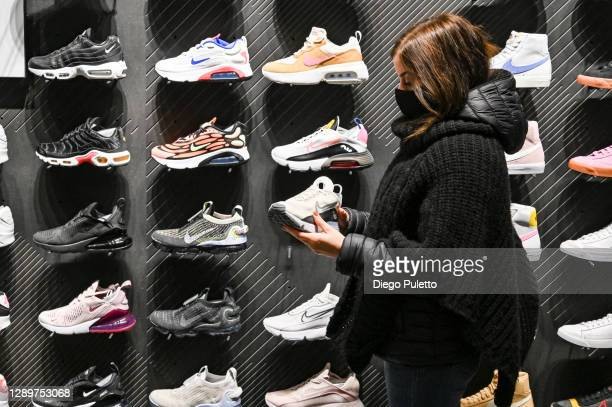 Person wearing a protective mask chooses shoes inside an Nike store, after reopening on December 06, 2020 in Turin, Italy. Italian regions lowered...