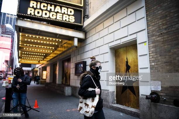 A person wearing a protective mask enters the staff and performers entrance of Richard Rodgers Theatre where the musical Hamilton is performed in the...