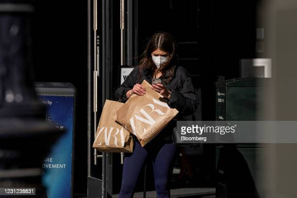 Person wearing a protective mask holds Zara shopping bags and looks at a mobile phone in San Francisco, California, U.S., on Wednesday, Feb. 17,...