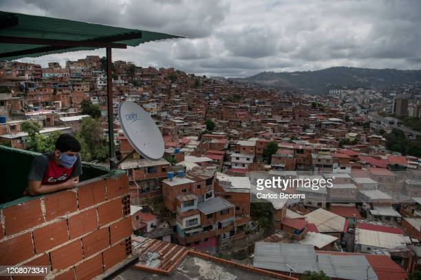 Person wearing a protective mask looks at Petare slum on March 23, 2020 in Caracas, Venezuela. While Nicolas Maduro declared national quarantine, the...
