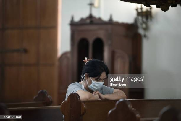 A person wearing a protective mask prays during a Palm Sunday mass in Caracas Venezuela on Sunday April 5 2020 Amid the coronavirus as the world's...