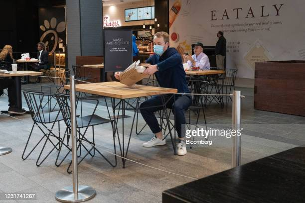 Person wearing a protective mask prepares to dine inside the food court at the Westfield Century City shopping mall in Los Angeles, California, U.S....