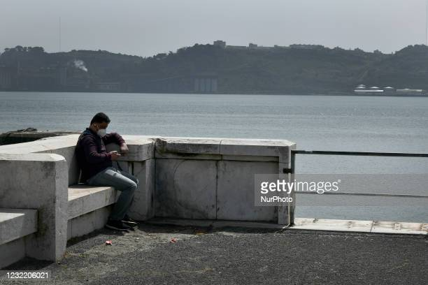 Person wearing a protective mask remains seated near the Bom Sucesso Dock, Lisbon, April 5, 2021. Portugal is currently experiencing a favorable...