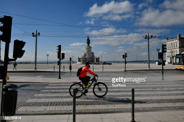 Person wearing a protective mask rides a bicycle near Praça de Comércio in Baixa district, Lisbon. 07 May 2021. Portugal added, in the last 24 hours,...