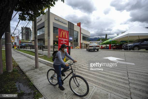Person wearing a protective mask rides a bicycle past a McDonald's Corp. Restaurant in San Salvador, El Salvador, on Friday, July 10, 2020. El...