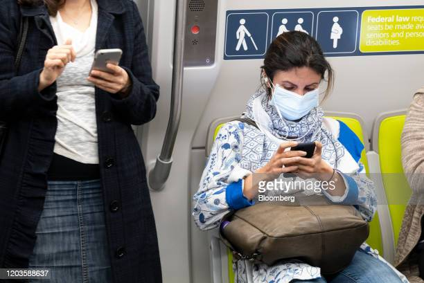 A person wearing a protective mask sits in a Bay Area Rapid Transit train car in San Francisco California US on Wednesday Feb 26 2020 President...