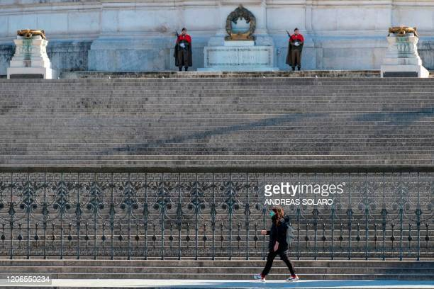 A person wearing a protective mask walks past guards in front of the closed Altare della Patria Vittorio Emanuele II monument in central Rome on...