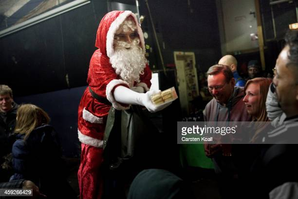 A person wearing a Santa Claus costume hands a gift to a guest at the 'Weihnachtsfest fuer alle' a Christmas celebration for the homeless at the YAAM...