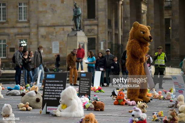 A person wearing a teddy bear costume is pictured during an urban intervention at Bolivar square in Bogota to protest against child abuse and to...