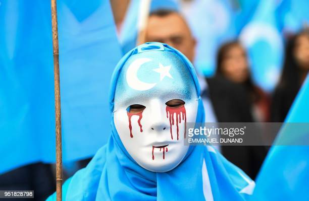 TOPSHOT A person wearing a white mask with tears of blood takes part in a protest march of ethnic Uighurs asking for the European Union to call upon...