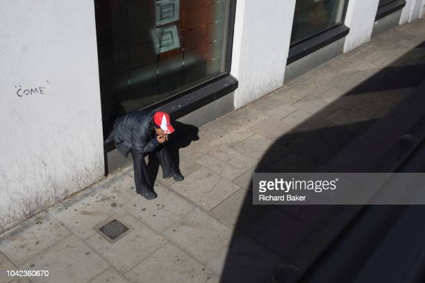 Person wearing an England cap looks down at the ground in Camberwell, on 26th September 2018, in Southwark, London, England.