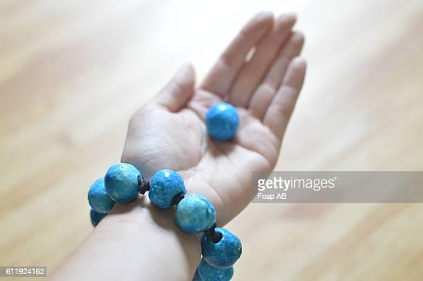 Person wearing bracelet holding bead