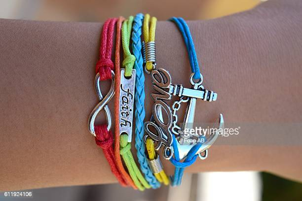 Person wearing bracelet with faith & love text