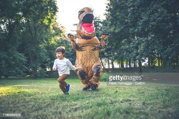 person wearing dinosaur costume chasing boy in park - dinosaur stock pictures, royalty-free photos & images