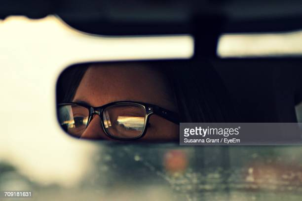 person wearing eyeglasses reflecting in rear-view mirror - rear view mirror stock pictures, royalty-free photos & images