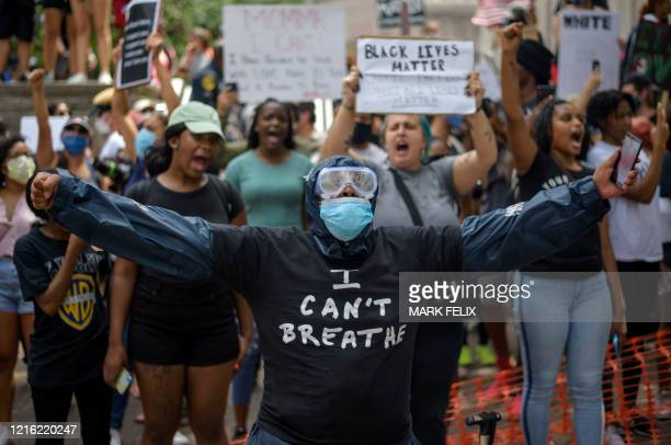 A person wearing facemask and goggles gestures as people gather to protest and mourn George Floyd a black man who died after a white policeman...