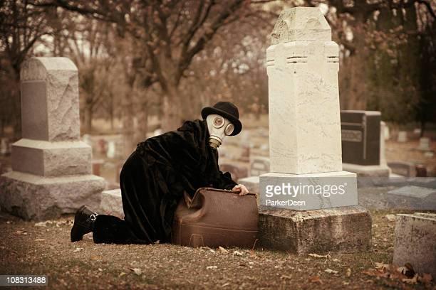 person wearing gas mask in cemetery with vintage doctor bag - dokterstas stockfoto's en -beelden