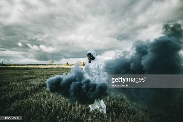 person mit gasmaske, die auf dem feld läuft - epidemic stock-fotos und bilder