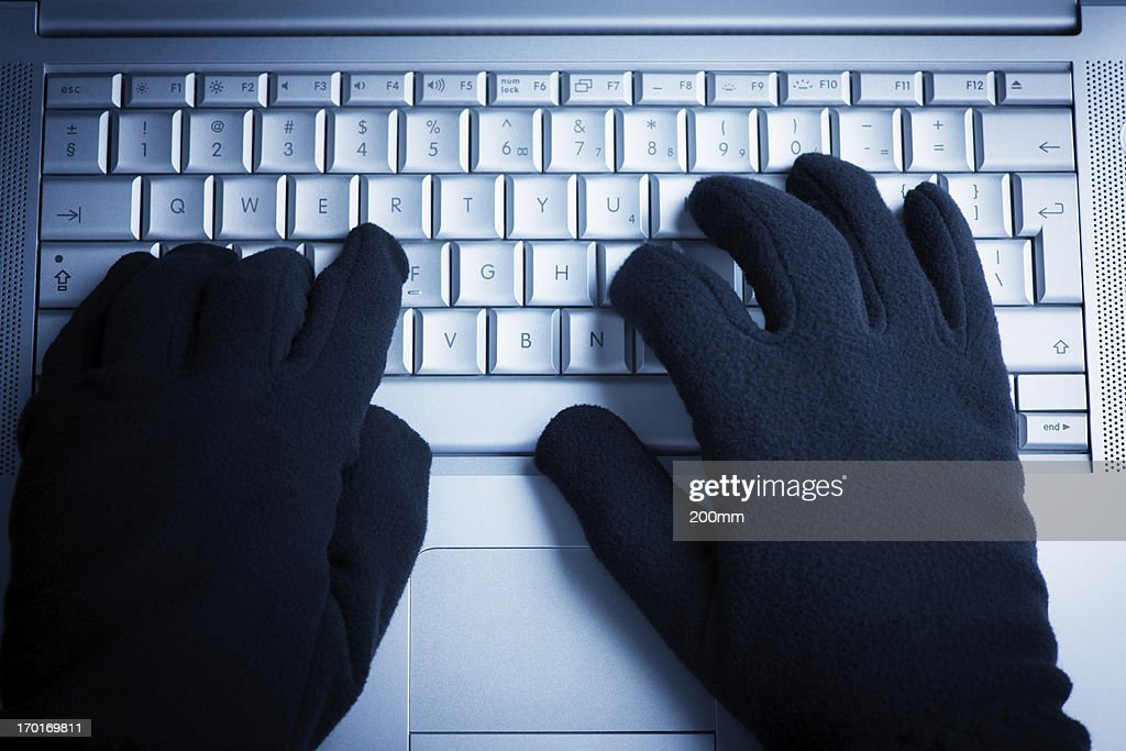A person wearing gloves while on the computer  : Stock Photo