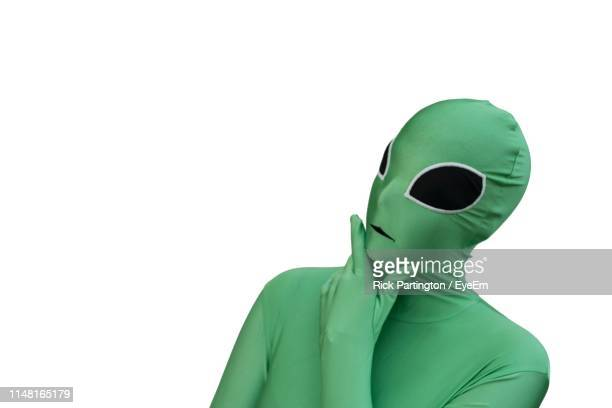 person wearing green costume standing against white background - alien stock-fotos und bilder