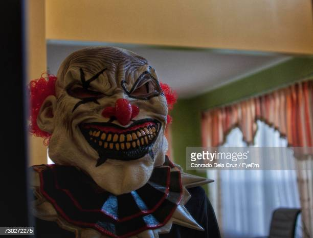person wearing mask at home - scary clown stock photos and pictures