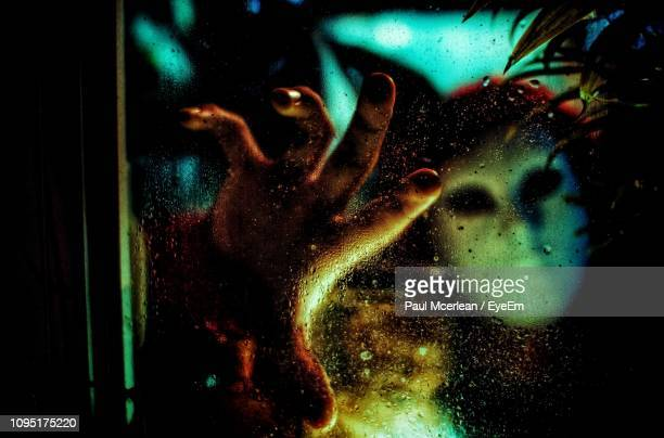 person wearing mask seen through wet glass window at night - scary face stock photos and pictures