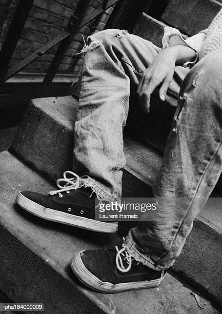 Person wearing old trousers, sitting on stairs, low section, b&w