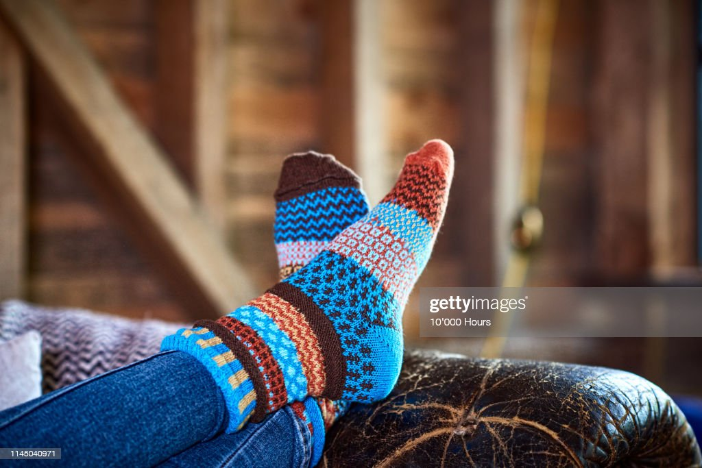 Person wearing patterned socks with feet up on leather sofa : Stock Photo