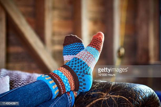 person wearing patterned socks with feet up on leather sofa - despreocupado imagens e fotografias de stock