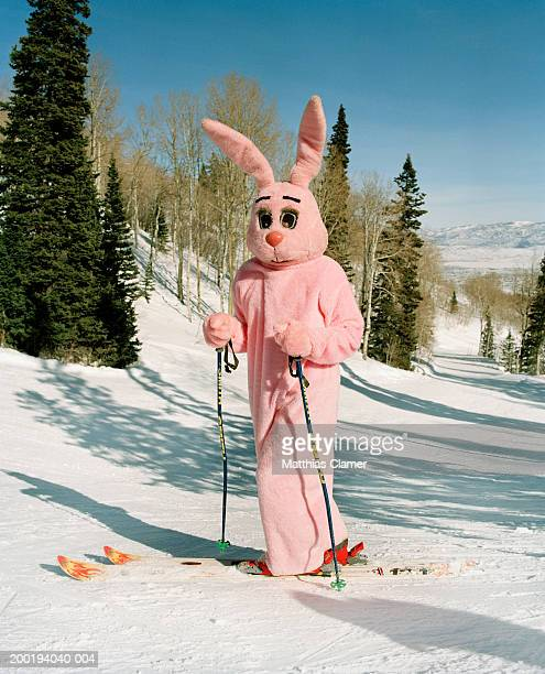 person wearing pink bunny costume on ski slope - ski humour photos et images de collection