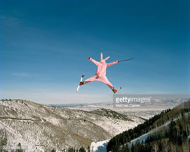 person wearing pink bunny suit ski jumping, rear view - image foto e immagini stock