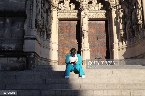 Person wearing protective face mask sits on the steps of The Cathedral of St. John the Divine during the coronavirus pandemic on May 26, 2020 in New...