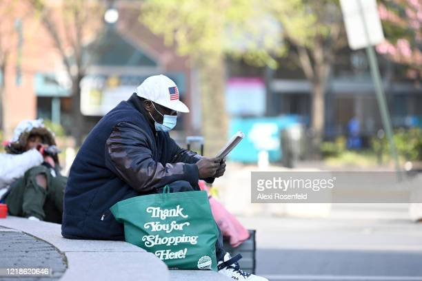 A person wearing protective mask sits and reads on the steps in Union Square amid the coronavirus pandemic on April 12 2020 in New York City United...