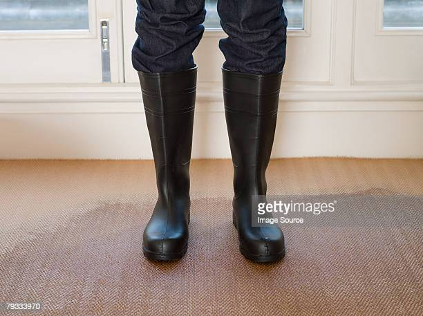 Person wearing rubber boots on a wet carpet