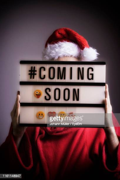 person wearing santa hat covering face with coming soon sign against gray background - coming soon stock pictures, royalty-free photos & images