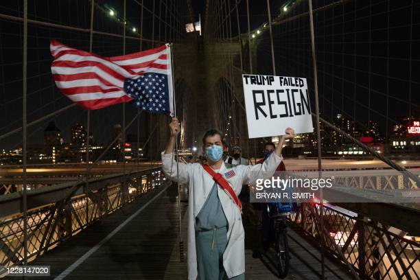 """Person wearing scrubs holds a placard and an upside down US flag during the """"March for the Dead"""" across the Brooklyn Bridge, in memory of those who..."""