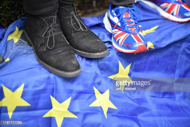 Person wearing Union Jack trainers stands on a European Union flag at Parliament Square as people prepare for Brexit on January 31, 2020 in London,...